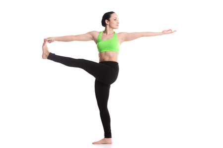 big toe: Serene sporty girl, doing fitness stretching exercises, standing in yoga posture utthita hasta Padangustasana, extended hand to big toe yoga pose, white background, isolated
