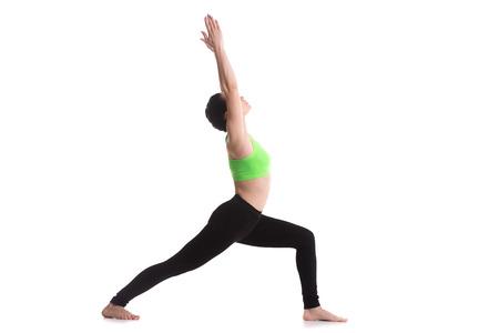 Sportief yoga meisje op een witte achtergrond doet lunge oefening, Warrior 1 houding, Virabhadrasana ik, weer voet op de vloer Stockfoto