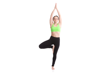 anjali: Sporty girl on white background doing exercise for spine, standing in asana Vrikshasana (Vriksasana, Tree Pose), hands above the head in anjali mudra, yoga for relieving stress Stock Photo