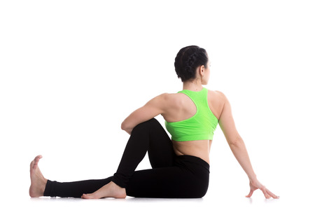 ardha: Beautiful sporty girl performing seated spinal twist, rear view of Half lord of the fishes pose, Ardha Matsyendrasana, yoga for back and hips