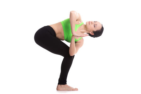 Slim sporty girl on white background standing in Revolved Chair asana, yoga pose Parivrtta Utkatasana, exercise for stretching spine, legs and abdomen training 版權商用圖片