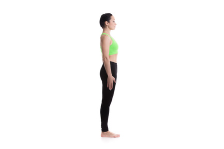 salutation: Sporty girl on white background performing basic standing asana tadasana, mountain yoga posture, pose from surya namaskar sequence, sun salutation complex Stock Photo