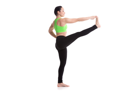 big toe: Sporty girl on white background standing in yoga position Utthita Hasta Padangushthasana, Extended Hand to Big Toe yoga pose (stretched hand grasps big toe)
