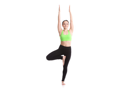 vriksasana: Serene smiling slim girl on white background doing exercise for spine flexibility, standing in Tree Pose, asana vrikshasana, Vriksasana, yoga for anxiety