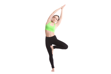 vriksasana: Sporty girl on white background doing fitness workout for spine, side bending in Tree Pose, asana vrikshasana, Vriksasana, yoga for stress