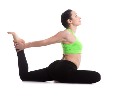 pada: Fitness girl on white background doing backbend eka pada rajakapotasana (one-legged King Pigeon yoga Pose), asana for flexible legs and spine