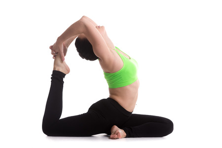 Athletic girl on white background sitting in eka pada rajakapotasana (One Legged Royal Pigeon Pose), asana for flexible legs and back