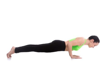 namaskar: Sporty girl doing exercises for shoulders on white background, push-ups, chaturanga dandasana (four-limbed staff pose), asana from surya namaskar sequence, sun salutation complex