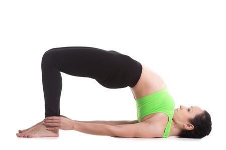 dvi: Beautiful sporty girl doing yoga workout, standing in bridge pose, dvi pada pithasana, setu bandhasana, set exercises for strengthening back and shoulders muscles