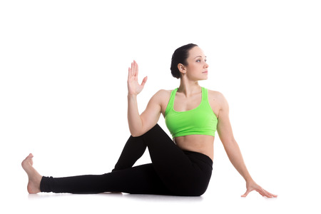 Beautiful athletic girl practicing seated spinal twist, Half lord of the fishes pose, Ardha Matsyendrasana, yoga for back and hips