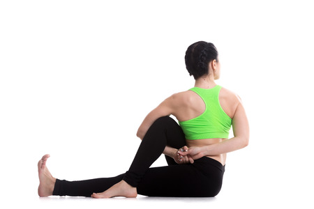 ardha: Beautiful sporty girl performing seated spinal twist, rear view of Half lord of the fishes pose, Ardha Matsyendrasana, yoga for back and hips, Deepened variation
