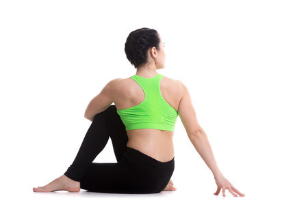 ligaments: Slim sporty girl practicing yoga, back view of Half lord of the fishes pose, Ardha Matsyendrasana, asana tones spinal nerves, ligaments, improves digestion