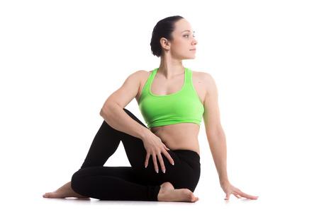 ardha: Attractive sporty girl doing yoga training, Half lord of the fishes pose, Ardha Matsyendrasana, one of the basic asana in Hatha Yoga