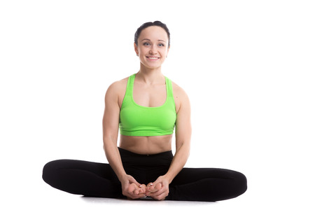baddha: Happy smiling sporty girl doing yoga training, bound angle posture, baddha konasana, cobbler pose