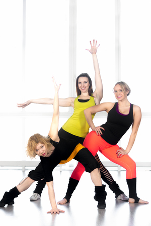 Group of three cheerful sporty young women doing aerobics exercises, modern dance movements in class. Active, healthy lifestyle, weight loss concepts photo