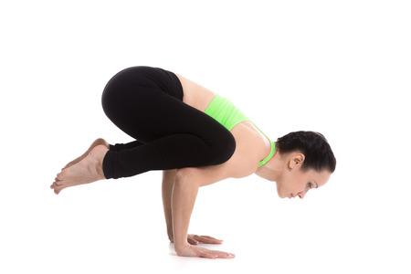 cuervo: Chica delgada deportiva haciendo parada de manos asana yoga, Crane (Crow) Pose, Bakasana para hombros, espalda superior, los brazos y las muñecas Foto de archivo