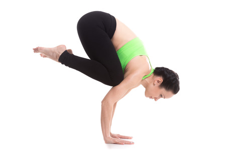 Beautiful sporty girl doing handstand yoga asana, Crane (Crow) Pose, Bakasana on straightened arms, pose for shoulders, upper back, arms and wrists Stock fotó