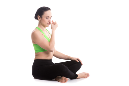 nostril: Calm beautiful girl practicing hatha yoga nadi shodhana pranayama (Alternate Nostril Breathing), sitting cross-legged in Easy Pose, Sukhasana, meditation, Vishnu mudra, copy space
