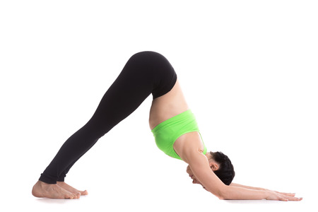 Sporty girl on white background stretching in Dolphin Yoga Pose, exercise for shoulders and flexibility