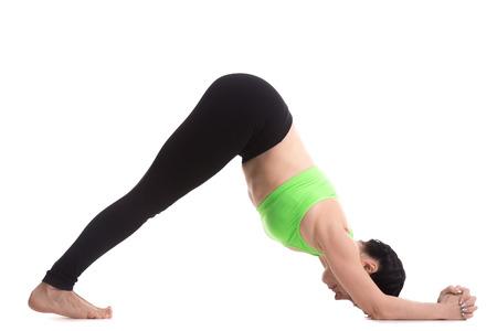 delfin: Sportowy dziewczyna na białym tle stoi w Dolphin asany jogi, stretching ramiona, ścięgna, łydki, łuki, wzmocnienie rąk i nóg