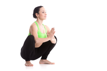 anjali: Smiling sporty girl on white background sitting in Garland yoga Pose, Malasana, yoga for stretching ankles, groins, back, strengthening belly, hands in Anjali Mudra (Salutation Seal)