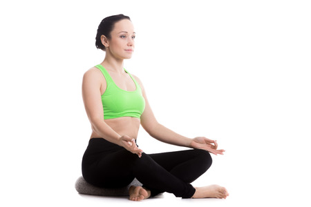 meditation isolated white: Serene girl practicing yoga, Sitting on pillow in Easy (Decent, Pleasant Pose), Sukhasana, asana for meditation, breathing, relieving stress, copy space Stock Photo