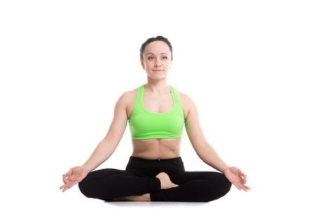 Serene fitness girl does yoga training, sitting in Ardha Padmasana, half lotus posture, Siddhasana, Accomplished Pose, asana for meditation, breathing exercises photo