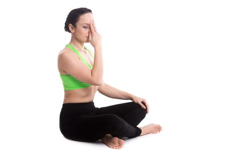 nostril: Serene girl practicing yoga nadi shodhana pranayama (Alternate Nostril Breathing), sitting in Easy (Decent, Pleasant Pose), Sukhasana, meditation, copy space Stock Photo
