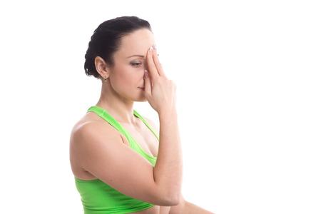 pranayama: Serene girl practicing yoga nadi shodhana pranayama (Alternate Nostril Breathing), meditating, hands in Smiling Buddha gesture, kapitthaka mudra for peace of mind, happiness, copy space Stock Photo