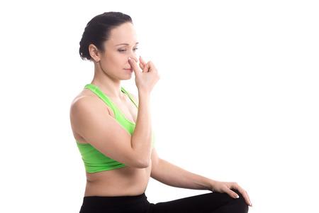 Vishnu Mudra voor hatha yoga Nadi Shodhan pranayama techniek, serene meisje beoefenen van yoga, mediteren, ademen door een neusgat, kopiëren ruimte