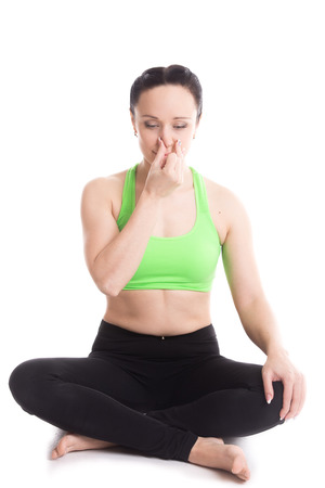 nostril: Calm beautiful girl practicing hatha yoga nadi sodhan pranayama (Alternate Nostril Breathing), sitting cross-legged in Pleasant Pose, Sukhasana, meditation, Vishnu mudra