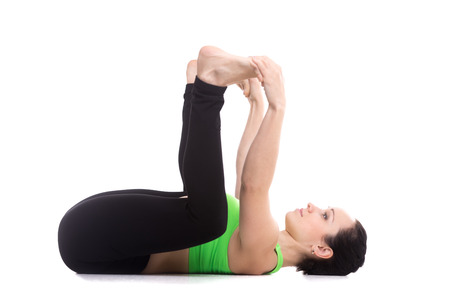 Sporty girl on white background lying in yoga Happy Baby pose, Ananda Balasana, relaxing, aligning back, stretching spine, legs, relieving stress and fatigue