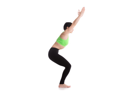 Sporty girl on white background standing in Chair yoga Pose (Fierce, Hazardous, Lightning Bolt, Wild, Awkward Posture), utkatasana, exercise for leg muscles Imagens