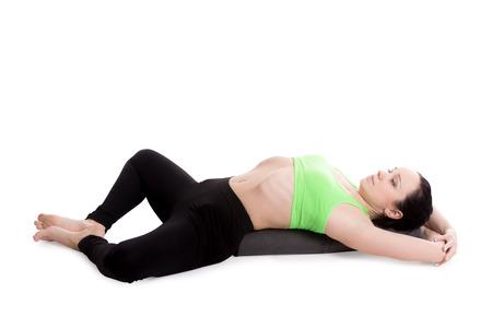 bolster: Sporty girl on white background resting in Reclining Bound Angle yoga Pose, Supta Baddha Konasana, restorative, relaxing asana, using bolster