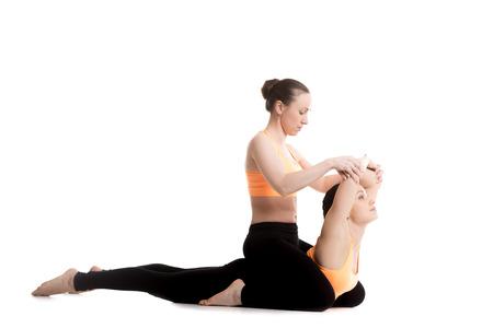 bhujangasana: Two beautiful sporty girls in orange sportswear practice yoga with partner, instructor teaches novice student, stretching exercises for spine, Cobra posture, bhudjangasana (Bhujangasana)