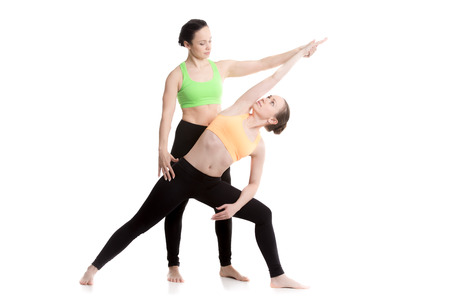 utthita: Two beautiful sporty girls practice yoga with partner, coach assists student, doing Extended Side Angle Pose, Utthita Parsvakonasana, therapeutic for low backache Stock Photo