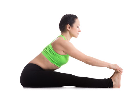 Athletic beautiful girl does yoga exercises, seated Forward Bend pose (Intense Dorsal Stretch), Paschimottanasana, stretching spine, shoulders, hamstrings photo
