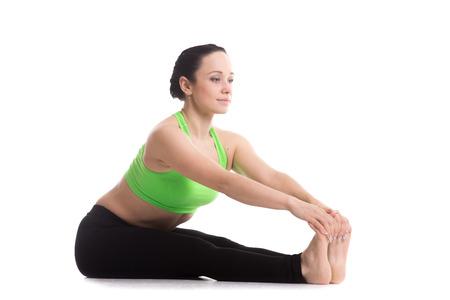 Serene fitness girl does yoga training, seated Forward Bend pose (Intense Dorsal Stretch), Paschimottanasana, stretching back, shoulders, hamstrings photo