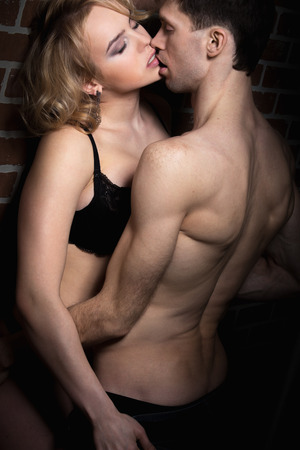 half naked: Erotic play of sexy young couple, half naked young man holding blond beautiful girl in black lingerie Stock Photo
