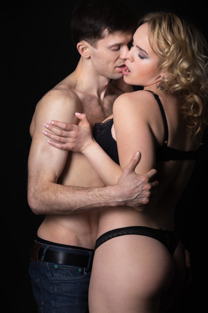 young couple sex: Sensual desire, beautiful half naked couple of lovers kissing, skin on skin, studio low key shot, black background