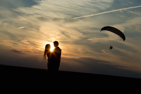 flying kiss: Couple of lovers against vast skyline on the sunset or sunrise, hugging each other, standing on the distance of a kiss, unusual date location, paraglider flying on the background