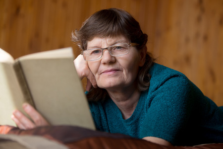 comfy: Beautiful elder woman in spectacles reading a book with faint smile, lying relaxed on bed at home in comfy bedroom with wooden walls, absorbed in interesting novel storyline