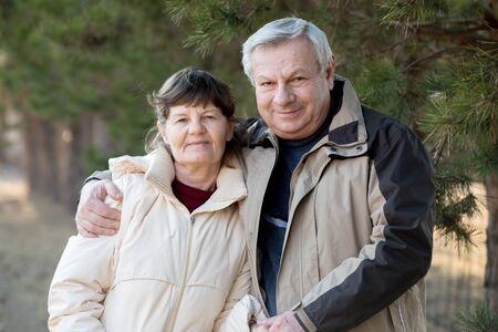 gentleness: Portrait of elder couple on a walk in park, senior man hugging his wife with gentleness