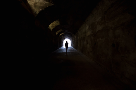 Person in dark tunnel, going towards the light. Hope, fear,