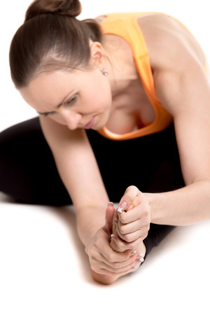 arthritis pain: Young athlete girl in sportswear touching aching foot, injured after sport practice, feeling pain in ligament, focus on leg and arms Stock Photo