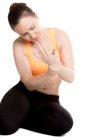 ligament: Young female athlete in sportswear touching aching wrist with unhappy expression, hurt after sport training, aching ligament, strained forearm