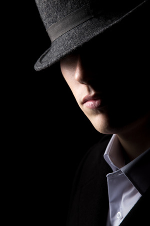 unknown men: Mysterious man in hat with half of his face in the shadows, minimalistic studio shot against black background, low key lighting