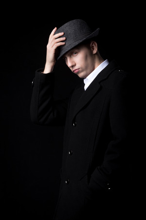 wicked: Brutal looking male person in the darkness, touching his hat, greeting with wicked, shrewd expression, low key studio shot