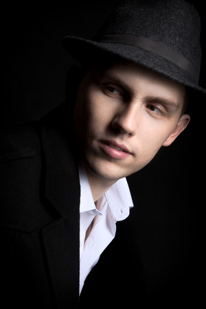 looking away from camera: Low key shot of young man in dark hat and coat on black background, looking away from camera