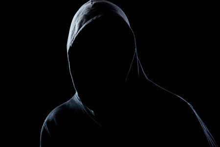 Young man in black hooded sweatshirt invisible in the night darkness, dimly lit, concepts of danger, crime, terror
